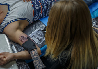 A blonde tattooist is portraying a tattoo on the arm of a client