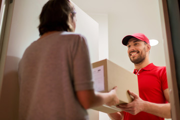 happy delivery man giving parcel box to customer