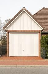 Garage mit weißem Tor und Spitzdach
