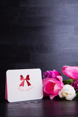 Bouquet of tender pink tulips with greeting card on black wooden background