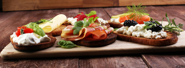 Bread Brushetta or authentic traditional spanish tapas set for lunch table. Sharing antipasti on party or summer picnic time over wooden rustic background.