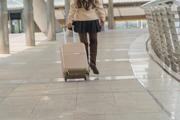 travel woman legs pulling suitcase bag walking along in modern city.