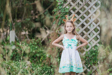 cute and quirky little girl standing in garden with giraffe ears on her head