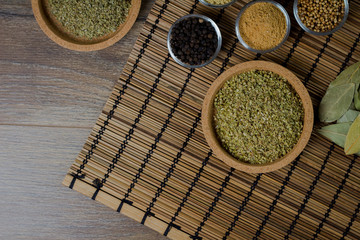Various spices in bowls with fresh seasoning on rustic wooden background, top view