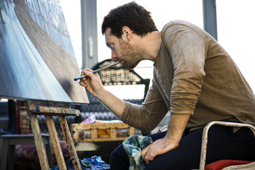 Young man painting while sitting indoors