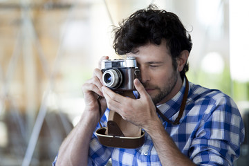 Man taking a photograph with a film camera