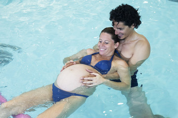 Pregnant woman exercising with help of partner in swimming pool