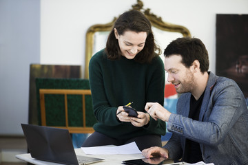 Woman sharing content of smartphone with colleague