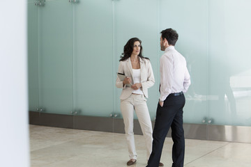 Businesswoman chatting with male colleague in office corridor