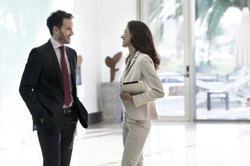 Business associates talking in office corridor