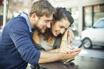 Couple sitting outdoors together, looking at smartphone
