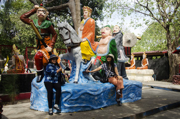 Thai woman sit and posing for take photo with Journey to the West statue