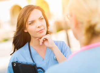 Two Young Adult Professional Female Doctors or Nurses Talking Outside.