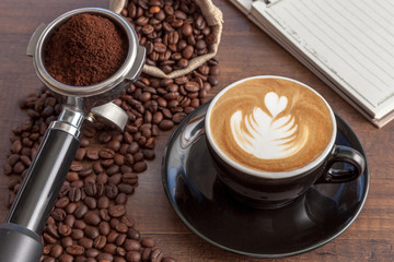 Wall Mural - Coffee cup of latte art in the black color cup with some coffee beans, portafilter and notebook on wooden background