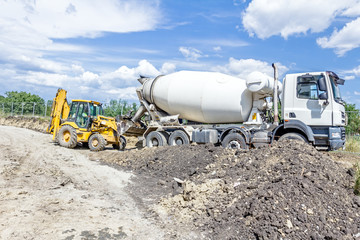 Truck mixer in process of pouring concrete into bulldozer scoop