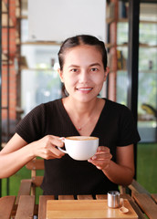Woman drinking hot coffee in the morning, with heart shape pattern on coffee cup.