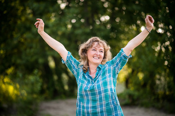 Carefree dancing mature woman against nature background