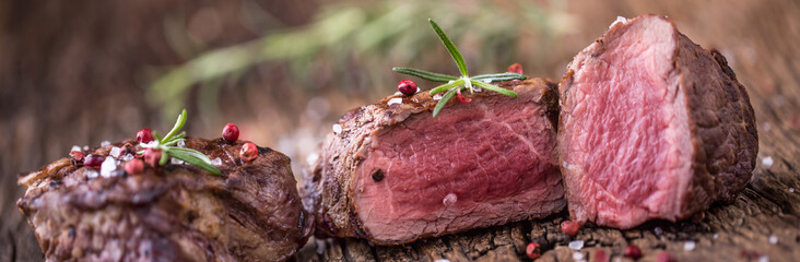 In de dag Steakhouse Grilled beef steak with rosemary, salt and pepper on old cutting board. Beef tenderloin steak.