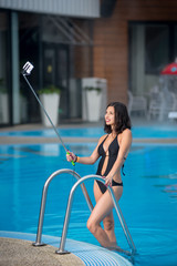 Attractive female in a black bikini posing against swimming pool, taking selfie photo with selfie stick on luxury resort with blurred background