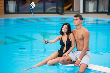 Young couple sitting on the edge of the swimming pool with perfect aqua water and taking selfie photo on the phone with selfie stick on the luxury resort