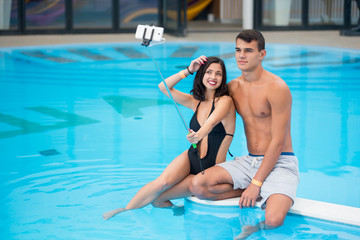 Young pair - man and woman sitting by the pool with perfect aqua water and making selfie photo on the phone with monopod on the luxury resort