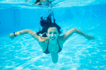 Underwater portrait of smiling female wearing in a black bathing suit in swimming pool, beautiful turquoise water. Close-up