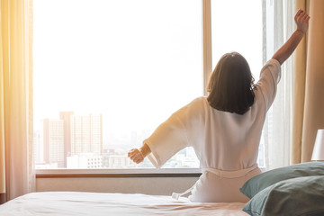Happy healthy woman's back view waking up stretching in bed room hotel/ home interior at glass wall window, city landscape background: Simple lifestyle people in cozy indoor comfortable relaxing space