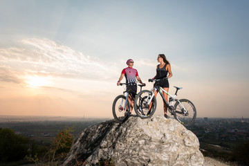 Man and woman standing on a rock with their bikes on the precipice of the cliff, looking to each other, under the evening sky at sunset. Below is a small city in the distance