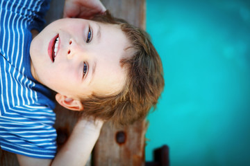 Dream for a whole life. The boy dreams, looking to the sky, lying on a wooden pier near the water of the Tiffany color