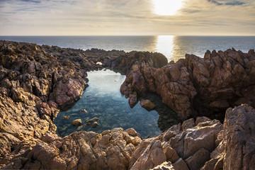 Cala Domestica Beach, natural pools at sunset in long exposure, Buggerru, Sardinia