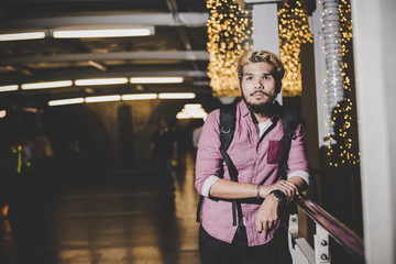 Handsome bearded man with backpack standing on the street while traveling at night.