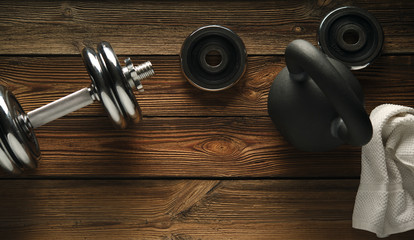 Top view of black iron kettlebell, dumbbell and white towel on wooden floor Sport background with copyspace