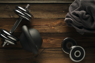 Top view of black iron kettlebell, dumbbell and grey towel on wooden floor Sport background with copyspace