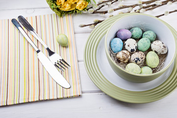 Quail eggs and pussy willow on white wooden table. Easter table setting. Spring holiday.