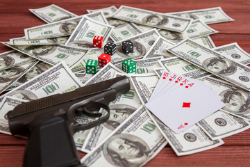 game cards and a pistol lying on dollar money banknotes. gambling casino poker winnings, crime, royal flush, gambling, jackpot.