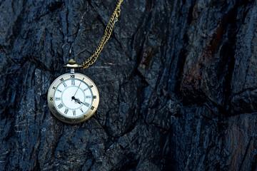 vintage golden pocket watch on rock