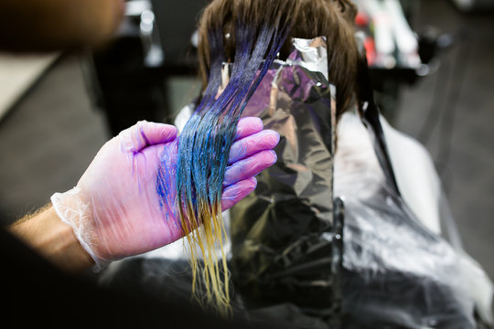 Man in gloves is dying long blue hair colorfull. Beauty salon, Barber.