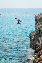 man cliff jumping into the sea in Cyprus