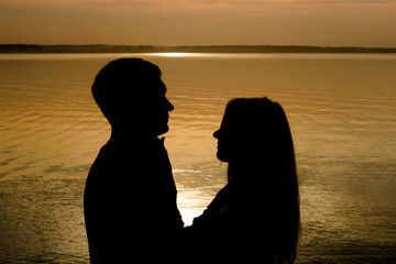 Image of silhouette of couple in love at sunset. Romantic dating couple on a beach in a colorful sunset in the background