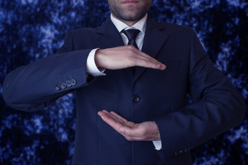 Businessman with cupped hands as if holding something.
