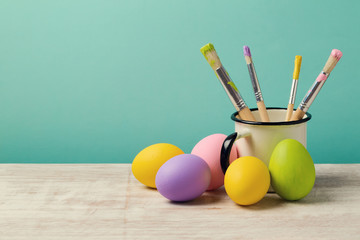 Easter holiday background with handmade painted eggs and brushes on wooden table