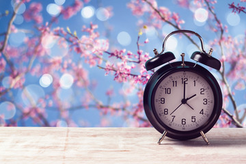 Spring time change concept with alarm clock over nature tree blossom background