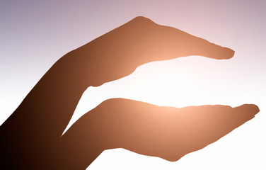 Raised hands catching sun on sunset sky. Concept of spirituality, wellbeing, positive energy etc.
