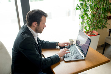 Man is sitting in cafe, enjoying cup of coffee and surfing net