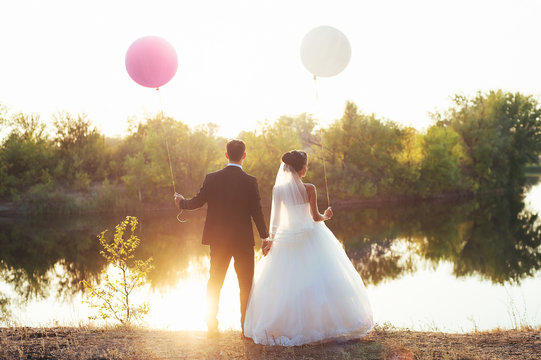Sunset. Newlyweds standing on the bank of the river holding hands. Balloons at the bride and groom.