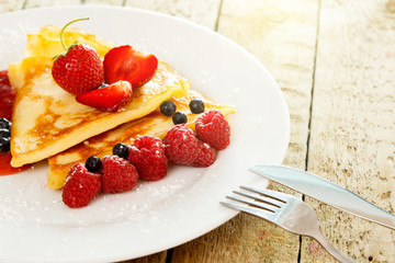 Pancakes with berries and sugar powder