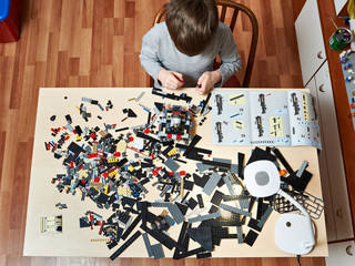 Boy plays and collects children plastic construction toys