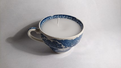 Candle in a China cup