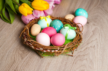 Easter composition of the branches, cakes, tulips colored eggs cooked for the holiday on the wooden background