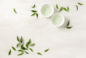Two white cups of tea, view from above background